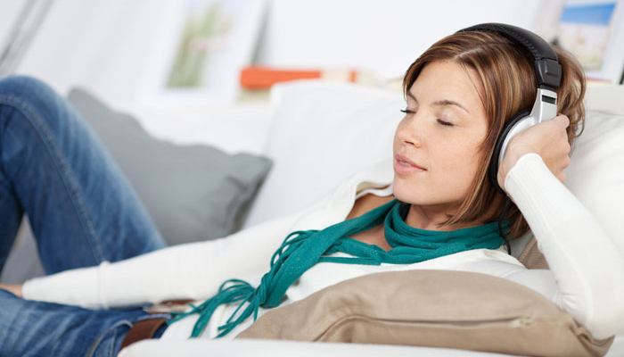 Woman relaxing on a sofa listening to music